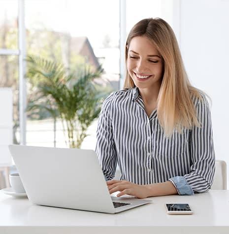 Woman looking at laptop smiling 2